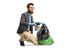 Individuo joven que pone una lata en un bolso de basura imagen de archivo