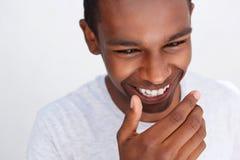 Individuo joven que ríe con la boca de la cubierta de la mano Imagen de archivo libre de regalías