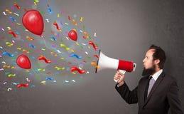 Individuo joven que se divierte, gritando en el megáfono con los globos Foto de archivo libre de regalías