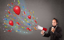 Individuo joven que se divierte, gritando en el megáfono con los globos Imagen de archivo libre de regalías
