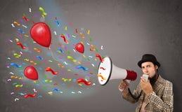 Individuo joven que se divierte, gritando en el megáfono con los globos Imagenes de archivo