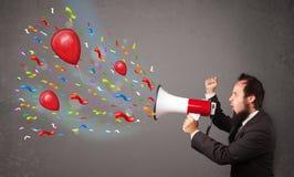 Individuo joven que se divierte, gritando en el megáfono con los globos Imagen de archivo