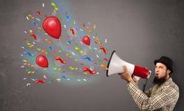 Individuo joven que se divierte, gritando en el megáfono con los globos Foto de archivo