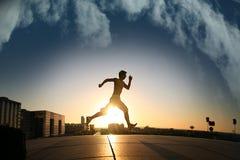 Individuo joven que se ejecuta durante puesta del sol imágenes de archivo libres de regalías