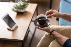 Individuo joven que se relaja mientras que bebe la bebida caliente en casa Fotos de archivo libres de regalías