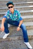 Individuo joven que se sienta con el cigarrillo Imagen de archivo libre de regalías
