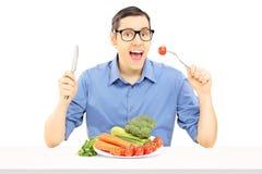 Individuo joven que se sienta en la tabla que come verduras Fotos de archivo