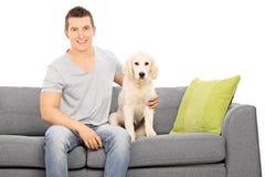 Individuo joven que se sienta en un sofá con un perrito lindo Imagenes de archivo