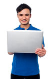 Individuo joven que sostiene el ordenador portátil Foto de archivo libre de regalías
