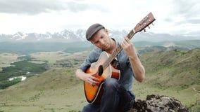 Individuo joven que toca la guitarra que se sienta en la hierba almacen de metraje de vídeo