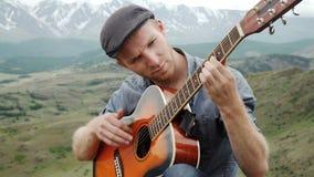 Individuo joven que toca la guitarra que se sienta en la hierba metrajes