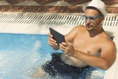 Individuo joven que usa el dispositivo de la tableta mientras que se relaja en la piscina Imágenes de archivo libres de regalías