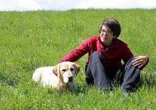 Individuo joven sonriente con su perro amarillo del labrador retriever Imagenes de archivo