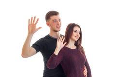 Individuo joven sonriente con una muchacha que lleva a cabo las manos en el top con las palmas Foto de archivo