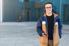 Individuo joven sonriente que escucha la música, sosteniendo el teléfono al aire libre Copie el espacio fotos de archivo