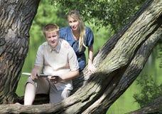 Individuo joven y la muchacha con los libros de texto en el banco del lago Fotos de archivo