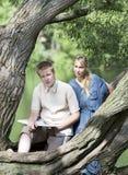 Individuo joven y la muchacha con los libros de texto en el banco del lago Imágenes de archivo libres de regalías