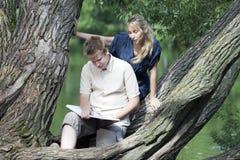 Individuo joven y la muchacha con los libros de texto en el banco del lago Fotos de archivo libres de regalías
