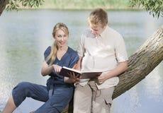 Individuo joven y la muchacha con los libros de texto en el banco del lago Imagen de archivo libre de regalías