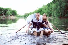 Individuo joven y muchacha sanos que salpican en agua Imagen de archivo