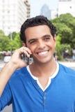 Individuo latino de risa con el teléfono celular en la ciudad Fotos de archivo libres de regalías
