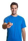 Individuo latino deportivo en una camisa azul que señala en la cámara Fotos de archivo