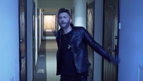 Individuo lindo con corte de pelo elegante y barba falsa en danzas del jaket en pasillo estrecho almacen de video