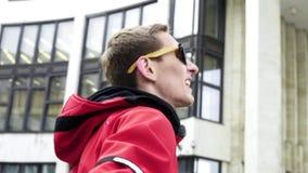 Individuo lindo en danzas rojas de la chaqueta y de las gafas de sol de deporte al lado de columnas del granito almacen de metraje de vídeo