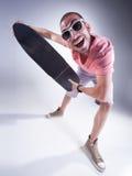 Individuo loco con un monopatín que hace caras divertidas Foto de archivo libre de regalías