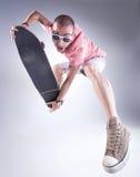 Individuo loco que salta con un monopatín que hace caras divertidas Fotos de archivo