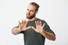 Individuo maduro hermoso con la barba que lleva a cabo las manos delante de él con la expresión mala que muestra al hombre en la  Imagen de archivo libre de regalías