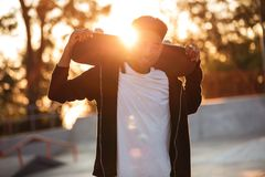 Individuo masculino feliz del adolescente que sostiene el monopatín en hombros Fotos de archivo