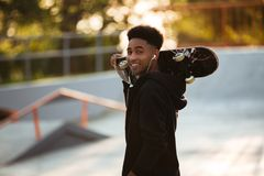 Individuo masculino joven sonriente del adolescente que sostiene el monopatín Imagen de archivo