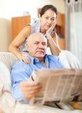 Individuo mayor con el periódico y la esposa madura Imagen de archivo