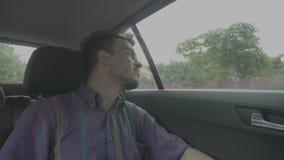 Individuo milenario enfocado del hombre que mira fuera de la ventana a la visión urbana que viaja en coche del uber a través de c almacen de video
