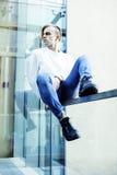 Individuo moderno joven del inconformista en el peinado rubio de la moda de la nueva universidad del edificio que se divierte, co Foto de archivo libre de regalías