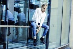 Individuo moderno joven del inconformista en el peinado rubio de la moda de la nueva universidad del edificio que se divierte, co Fotografía de archivo
