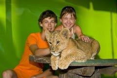 Individuo, muchacha y león joven Fotos de archivo
