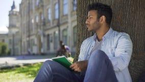 Individuo multinacional que se sienta debajo de árbol, escribiendo en el cuaderno, pensando, compositor almacen de metraje de vídeo