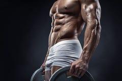 Individuo muscular del culturista que hace ejercicios con el disco de la pesa de gimnasia foto de archivo