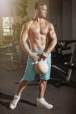 Individuo muscular del culturista que hace ejercicios con el peso en gimnasio fotografía de archivo libre de regalías