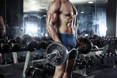 Individuo muscular del culturista que hace ejercicios con pesa de gimnasia grande Imágenes de archivo libres de regalías
