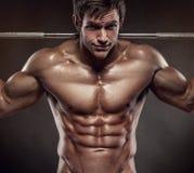Individuo muscular del culturista que hace ejercicios con pesas de gimnasia sobre bla imagen de archivo