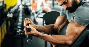 Individuo muscular del culturista que hace ejercicios en gimnasio imagen de archivo