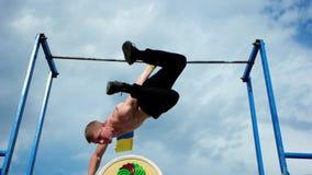 Individuo muscular fuerte que hace el atletismo de los ejercicios en una barra transversal transversal almacen de metraje de vídeo