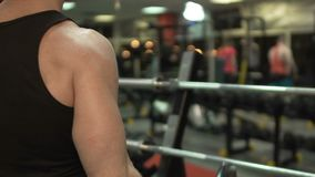 Individuo muscular que hace elevación-UPS con la barra del rizo en el gimnasio, entrenamiento activo, levantamiento de pesas metrajes