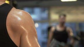 Individuo muscular que levanta las pesas de gimnasia grandes delante del espejo, entrenamiento activo en gimnasio almacen de metraje de vídeo