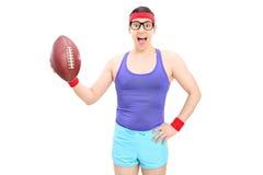 Individuo nerdy emocionado que lleva a cabo un fútbol Imagenes de archivo
