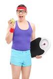 Individuo Nerdy que come la manzana y que sostiene una escala del peso Imagen de archivo libre de regalías