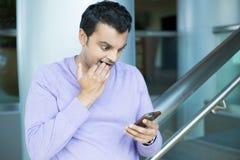 Individuo nervioso que ve malas noticias en el teléfono imagenes de archivo